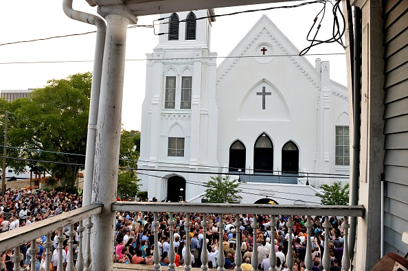 People line up to lay flowers at Emanuel AME Church in Charleston, South Carolina, on June 19, 2015. Police captured the white suspect in a gun massacre at one of the oldest black churches in the United States, the latest deadly assault to feed simmering racial tensions. Police detained 21-year-old Dylann Roof, shown wearing the flags of defunct white supremacist regimes in pictures taken from social media, after nine churchgoers were shot dead during bible study on June 17. AFP PHOTO/MLADEN ANTONOV        (Photo credit should read MLADEN ANTONOV/AFP/Getty Images)